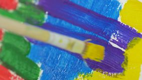 Sluit omhoog de borstel die van de kunstenaarsverf een verf met mooie kleuren kleuren stock footage