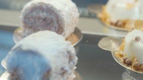 Sluit omhoog de cakes van het chocoladebroodje en witte vanillepudding in de glasvitrine in de winkel stock video
