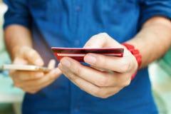 Sluit omhoog de creditcard van de mensenholding en gebruiks slimme telefoon met shoppi Stock Fotografie