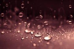 Sluit omhoog de dalingen die van het regenwater op blauwe sponsoppervlakte zoals vallen Stock Afbeelding