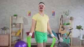 Sluit omhoog de grappige actieve mens van de jaren '80 met een snor thuis belast met geschiktheid met behulp van elastiekjes stock footage