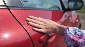 Sluit omhoog De hand van de vrouw glijdt zacht langs het lichaam van de auto 4K langzame mo stock footage