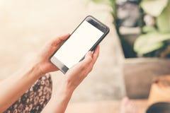 Sluit omhoog de holding van de handvrouw en het gebruiken van telefoon in tuin Royalty-vrije Stock Foto