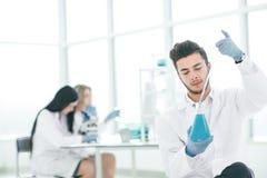 Sluit omhoog de jonge wetenschapper maakt de analyse van de vloeistof in de fles royalty-vrije stock afbeeldingen
