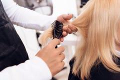 Sluit omhoog De kapper` s handen kammen uit recht blondehaar van vrouw door haarborstel stock afbeelding