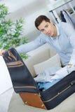 Sluit omhoog de kleren van de zakenmanverpakking in reiszak Royalty-vrije Stock Fotografie