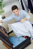 Sluit omhoog de kleren van de zakenmanverpakking in reiszak Royalty-vrije Stock Foto