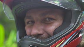 Sluit omhoog de mens die van de gezichtsmotorrijder in motohelm aan camera en het glimlachen kijken De fietsermens van portretmot stock video