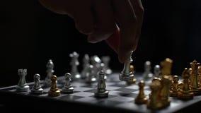 Sluit omhoog de mens die zilveren de nederlaagvijand van het koningsschaak op schaakbord bewegen stock video