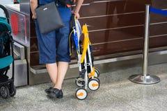 Sluit omhoog de mens met babywandelwagen bij incheckbalie bij luchthaven Concept familiereis met baby stock fotografie