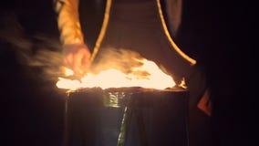Sluit omhoog De mens speelt brandende trommel Tegen de achtergrond van opvlammende lichten stock videobeelden