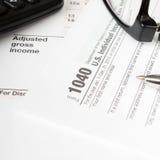 Sluit omhoog de muntachtergrond van de V S Individuele belastingsvorm 1040 Stock Foto's
