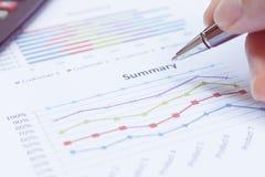 Sluit omhoog de pen van de zakenmanholding is op rapport en calcul Royalty-vrije Stock Afbeelding