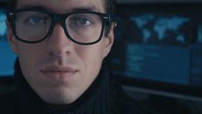 Sluit omhoog de programmeur van de Portrethakker in glazen in het donkere die centrum van de cyberveiligheid met de vertoningssch stock footage