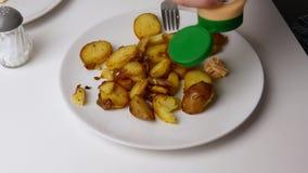 Sluit omhoog De saus van de fles wordt gegoten op een plaat naast de gebraden aardappels Het concept van het voedsel stock footage
