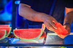 Sluit omhoog de snijdende watermeloen van de fruitverkoper voor verkoop op straat in B royalty-vrije stock afbeeldingen