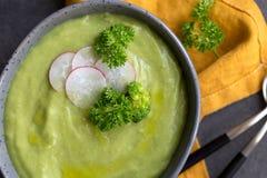 Sluit omhoog de soep van de broccoliroom met radijs en lepel op grijze achtergrond stock foto