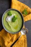 Sluit omhoog de soep van de broccoliroom met radijs en lepel op grijze achtergrond stock fotografie