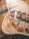 Sluit omhoog de toost van het chocoladebovenste laagje op houten plaat royalty-vrije stock afbeeldingen