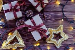 Sluit omhoog de vakjes van de Kerstmisgift in ambachtdocument met satijnlinten en vakantiedecoratie op de donkere houten achtergr Royalty-vrije Stock Foto's