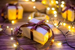 Sluit omhoog de vakjes van de Kerstmisgift in ambachtdocument met satijnlinten en vakantiedecoratie op de donkere houten achtergr Stock Foto's