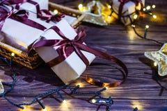 Sluit omhoog de vakjes van de Kerstmisgift in ambachtdocument met satijnlinten en vakantiedecoratie op de donkere houten achtergr Stock Afbeelding