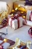 Sluit omhoog de vakjes van de Kerstmisgift in ambachtdocument met satijnlinten en vakantiedecoratie op de donkere houten achtergr Royalty-vrije Stock Afbeeldingen