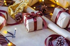 Sluit omhoog de vakjes van de Kerstmisgift in ambachtdocument met satijnlinten en vakantiedecoratie op de donkere houten achtergr Royalty-vrije Stock Afbeelding