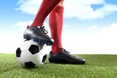 Sluit omhoog de voetbalster die van benenvoeten in rode sokken en zwarte schoenen met bal op grashoogte in openlucht spelen stock foto's