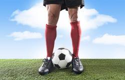 Sluit omhoog de voetbalster die van benenvoeten in rode sokken en zwarte schoenen met bal op grashoogte in openlucht spelen stock foto