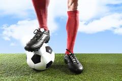 Sluit omhoog de voetbalster die van benenvoeten in rode sokken en zwarte schoenen met bal op grashoogte in openlucht spelen royalty-vrije stock foto
