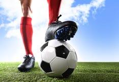 Sluit omhoog de voetbalster van benenvoeten in rode schokken en zwarte schoenen die met bal stellen die op gras zich in openlucht stock afbeelding