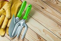 Sluit omhoog de vork van de meningstuin en handspade met gele handschoenen op houten raad royalty-vrije stock foto