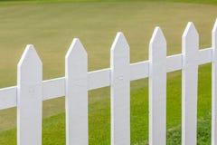 Sluit omhoog de witte houten omheiningen met vaag groen gebied in bac stock foto's