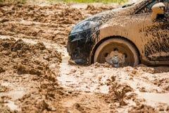 Sluit omhoog de zwarte die auto in de modder wordt geplakt kan niet uit de modder vallen Royalty-vrije Stock Afbeelding