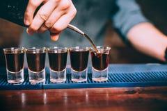 Sluit omhoog details van barman die alcoholische drank in kleine glazen gieten bij verjaardagspartij Stock Afbeelding