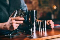 Sluit omhoog details van barmanhanden gebruikend cocktailhulpmiddelen Professionele barman die bij bar werken Stock Foto's