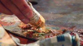 Sluit omhoog details van gele olieverf op een kunstenaarspallet stock videobeelden