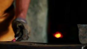 Sluit omhoog dia van smid wordt geschoten die heet steelt met een hamer in spijker die vormt stock videobeelden