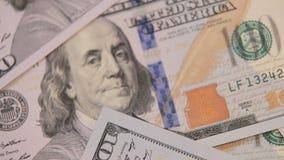 Sluit omhoog dollyschot van verspreide Amerikaanse papiergeldrekeningen de achtergrond van het contant geldgeld Benjamin Franklin stock footage