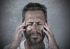 Sluit omhoog dramatisch portret van de jonge aantrekkelijke bezorgde en gedeprimeerde mens in pijn met handen op zijn hoofd lijde stock foto's