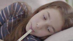 Sluit omhoog droevig ziek meisje liggend in bed met een thermometer in mond r Geneeskunde en gezondheid stock video