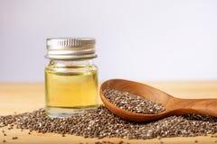 Sluit omhoog een etherische olie en de zaden van Chia in houten lepel, een supe Royalty-vrije Stock Foto's