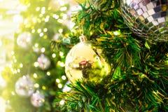 Sluit omhoog Een gouden gift hangt op chrismasboom Vage achtergrond stock foto's