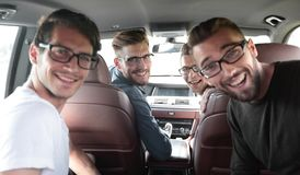 Sluit omhoog een groep vrienden die in de auto zitten stock foto's