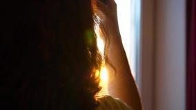 Sluit omhoog Een jong Meisje komt aan het venster en kleedt hoofdtelefoons om aan muziek te luisteren Vage achtergrond met zonson stock footage