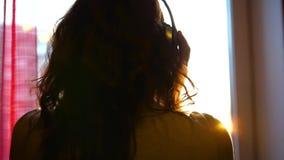 Sluit omhoog Een jong Meisje komt aan het venster en kleedt hoofdtelefoons om aan muziek te luisteren Vage achtergrond met zonson stock videobeelden