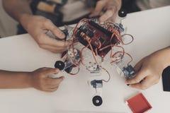 Sluit omhoog Een jonge kerel verzamelt een robot Hij wordt geholpen door twee kleine jongens Close-up van de ontmantelde robot royalty-vrije stock afbeeldingen