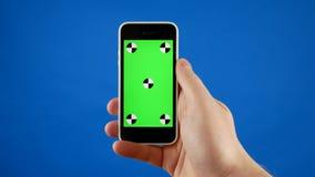 Sluit omhoog Een man hand houdt een smartphone met het groen scherm en maakt het jatten, het raken en het scrollen gebaren Blauw stock video