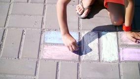 Sluit omhoog, een meisje in zonnebril, trek tekeningen met kleurpotloden op het asfalt, straattegels Een hete de zomerdag stock videobeelden